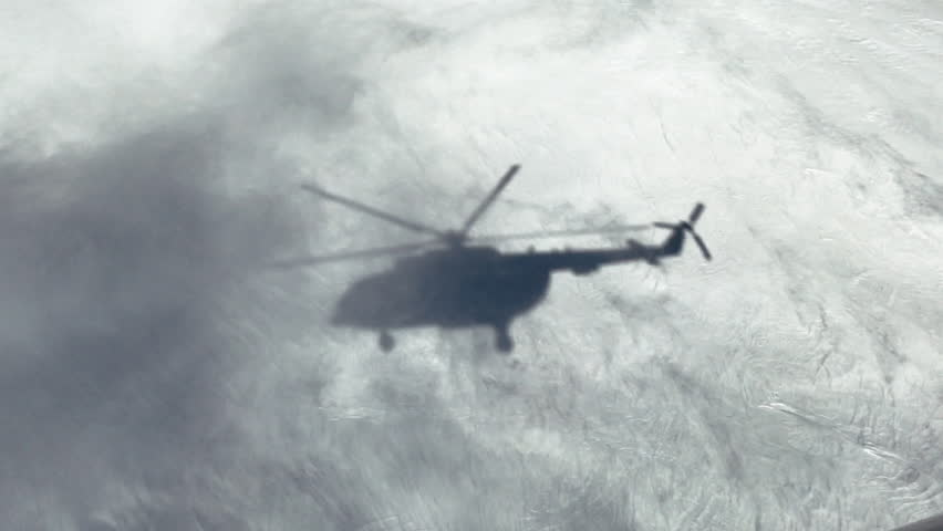 Silhouette of a helicopter in the snow Heliskiing