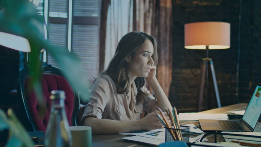Upset business woman using phone in cozy studio. Depressed businesswoman calling phone in office. Female manager business calling at workplace. Angry girl at workplace in evening