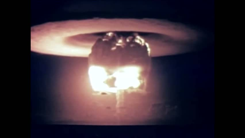 CIRCA 1954 - A nuclear device is detonated from a firing barge and the resulting mushroom cloud is shown at Bikini Atoll. | Shutterstock HD Video #1009420976