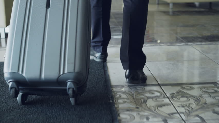 Dolly shot of legs of businessman walking through hotel lobby pulling luggage and stop at reception desk. Business, travel and people concept