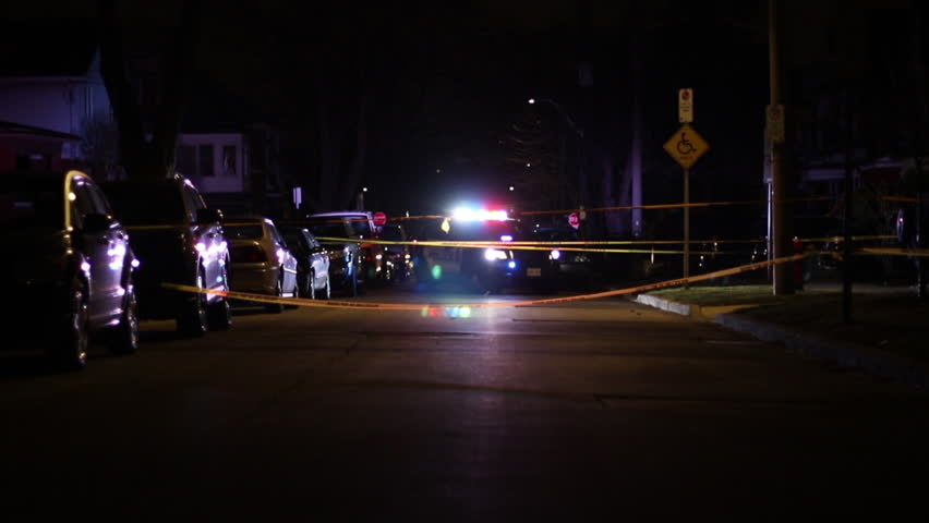 Police car with flashing lights at a taped off crime scene at night on a city street.  Police crime scene investigation.    Shutterstock HD Video #1009440884