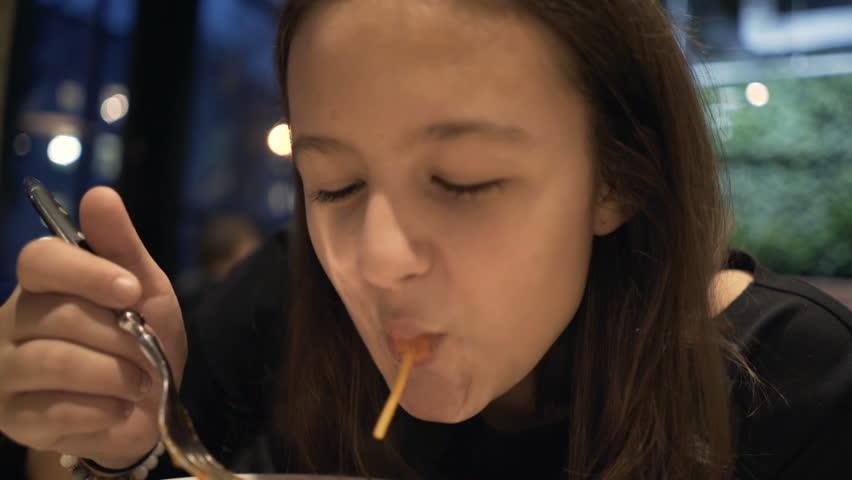Teenage girl eating meal, spaghetti sitting in cafe   #1009449845