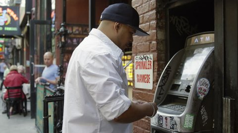 NEW YORK - MAY 17, 2015: Hispanic man with hat making withdrawal from ATM cash machine, slow motion 4K, Greenwich Village Manhattan NY. Greenwich Village is a famous neighborhood in NYC, USA.