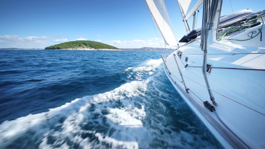 Yacht sailing at the sea of Croatia. Sailboat in windy conditions cruising clear blue ocean water. Large white Yacht with drawn sails / canvas.