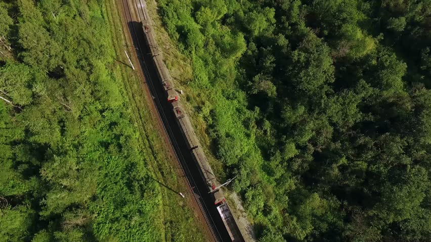 Freight train carries an electric locomotive by two-sided winding Trans Siberian railways with railroad crossing  in the Ural Mountains - Aerial Photography, top view