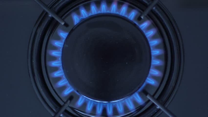 Kitchen burner turning on.Stove top burner igniting into a blue cooking flame.  Natural gas inflammation, close up.  | Shutterstock HD Video #1009467308