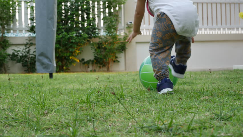 slow-motion, cute child toddle falling on green grass playing ball #1009469399