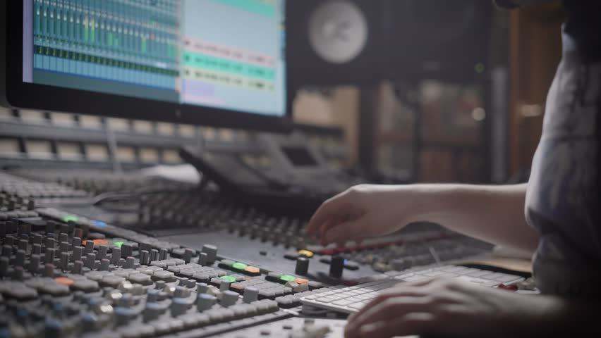 Talanted dj is creating music in a recording studio on a mixing console.   Shutterstock HD Video #1009470308