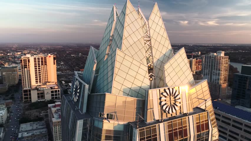 This is an rotating aerial shot of the frost tower in Austin, Texas at sunset.