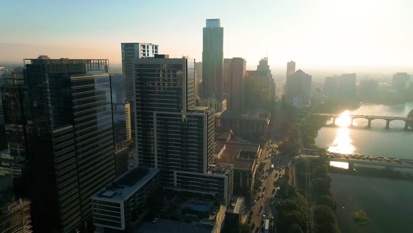 This is a lowering aerial shot of downtown Austin along Cesar Chavez at Sunset.