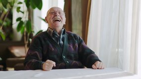 Happy senior man laughing while sitting at table