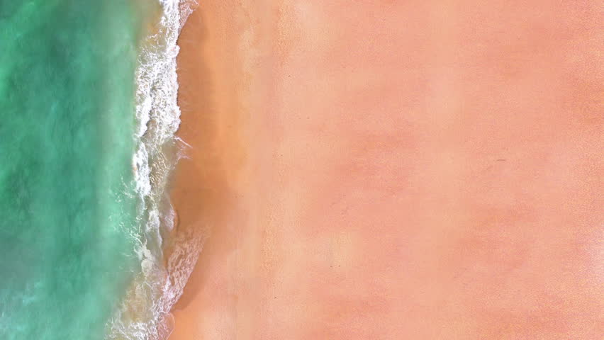 Aerial view of sand beach. Looping ocean texture, Top view sea waves slow motion, flying over tropical sandy beach and waves, Sunset  beach seamles loop.
