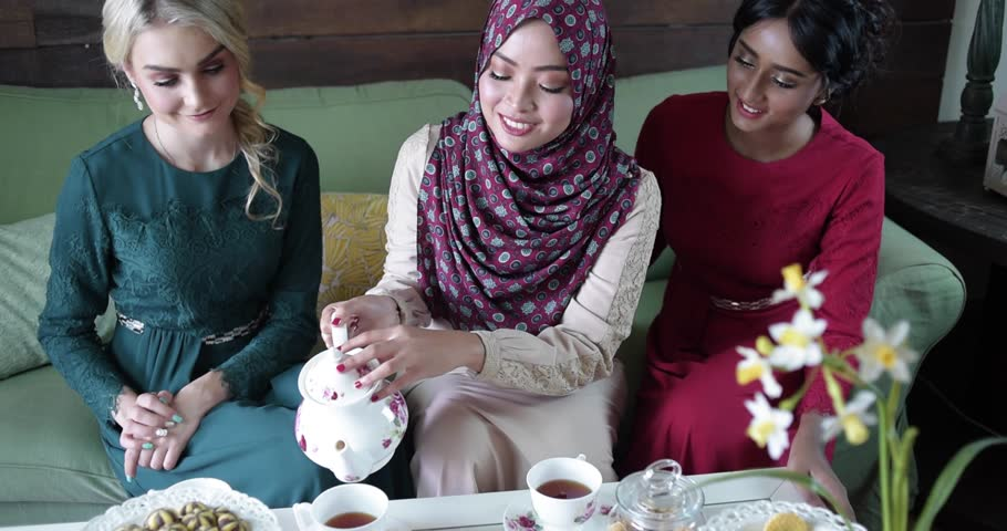 Beautiful happy female model during Hari Raya open house.Muslim girl wearing hijab with friends having tea and cookies during Eid ul-Fitri celebration.Professional model/actor. Royalty-Free Stock Footage #1009493771