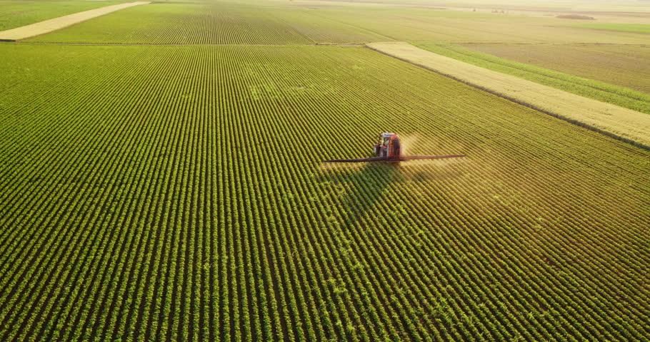 Aerial drone shot of a farmer spraying soybean fields #1009501754