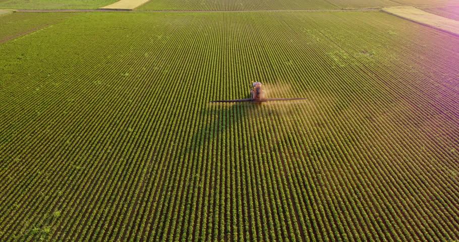 Aerial drone shot of a farmer spraying soybean fields #1009501757