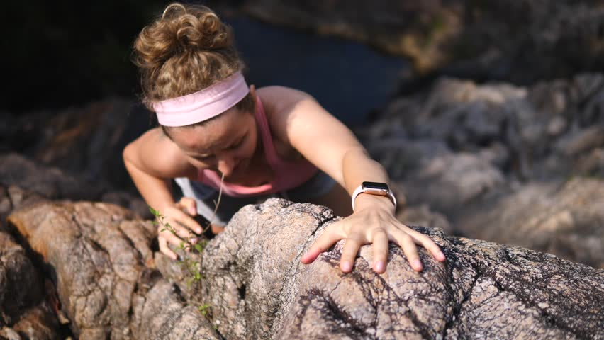 Sports Woman With Smartwatch Climbing The Rock Having Workout In Mountains