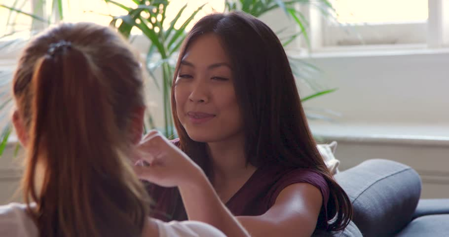 Single shot of asian woman talking to her friend on the sofa, camera captures flare occasionally. Other shots available for scene. Royalty-Free Stock Footage #1009513691
