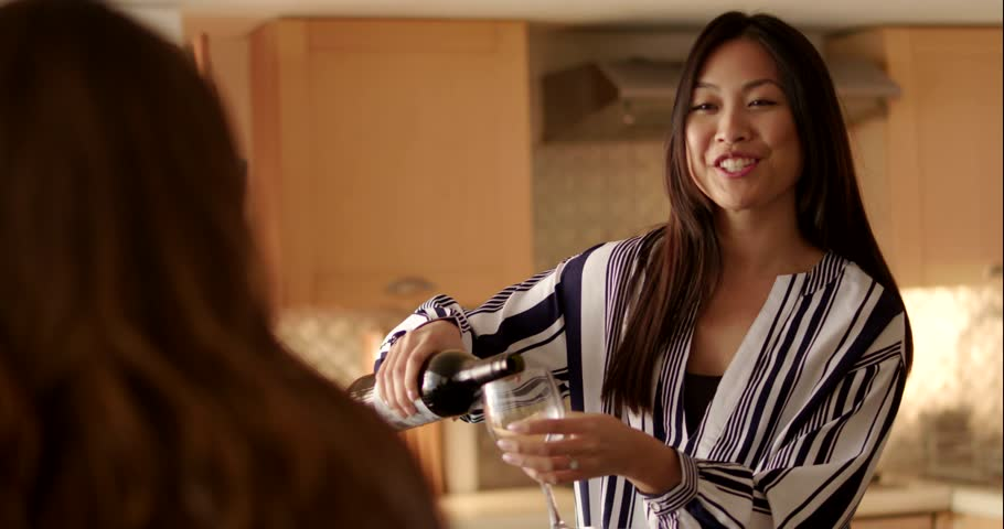 Asian woman pours a glass of wine and hands it to her friend.  Royalty-Free Stock Footage #1009513697