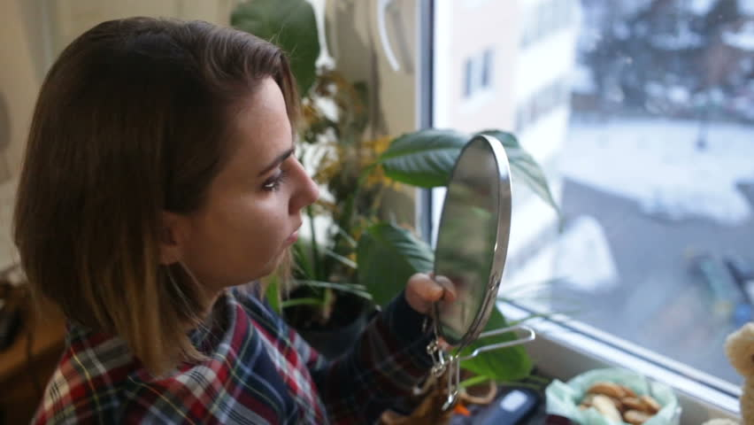 The girl looks to smear a mirror with fingermarks. Top-down view, closeup, sunset, natural light, indoors, real time #1009516547