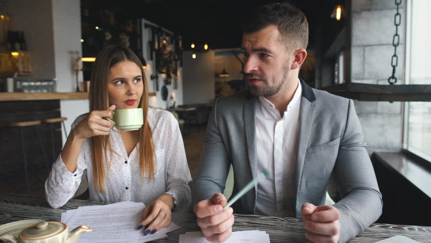 young business man and woman sitting in cafe and discussing contract