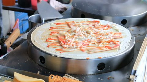 A hand is making crepes outdoors, Cooking of crepes pancakes with topping, dried shredded pork, ketchup, chilli sauce, mayonnaise, chocolate in hot pan at street market  Thai and Japanese dessert.