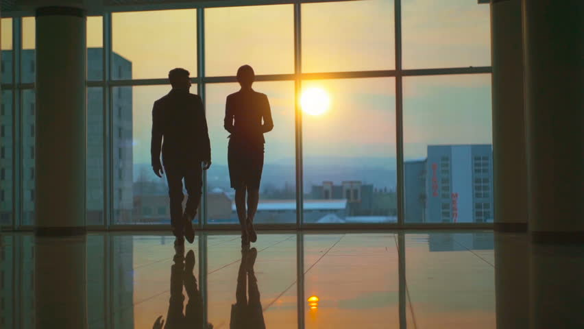 The man and woman walking in the office hall on a sunset background. slow motion | Shutterstock HD Video #1009530023