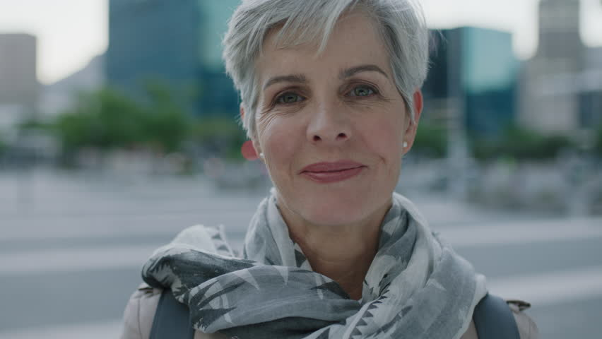 close up portrait of mature caucasian business woman looking at camera smiling cheerful in urban city background wearing scarf real people series #1009537805