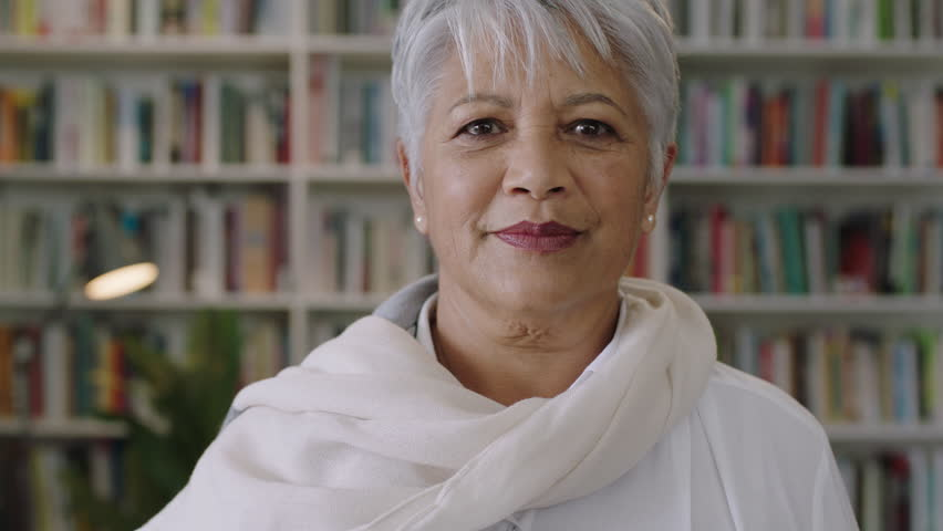 Portrait of friendly indian middle aged teacher standing in library smiling | Shutterstock HD Video #1009563494