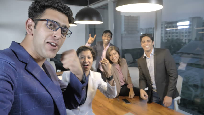 An attractive, young and dynamic businessman of startup firm taking a selfie with team members in a modern office. Energetic and cheerful associates   enjoying themselves a selfie picture with a boss | Shutterstock HD Video #1009576823