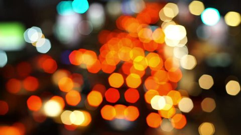 Abstract blur, de-focus of moving vehicles bokeh traffic lights on a busy street at night time