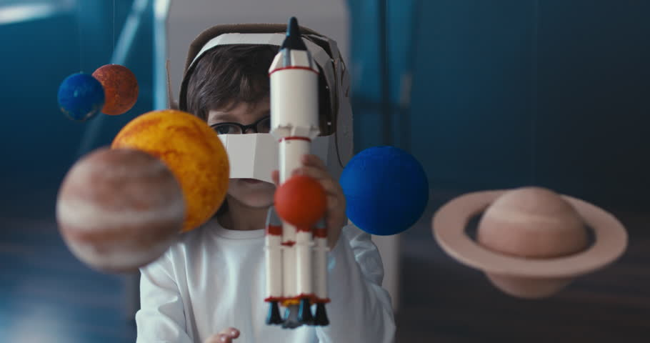 CU Cute little boy wearing cardboard astronaut helmet flying toy rocket through planets, exploring deep space. 4K UHD 60 FPS SLOW MO | Shutterstock HD Video #1009606277