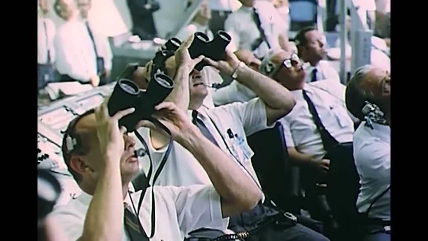 CIRCA 1969 - Men at launch control watch Apollo 11's progress through binoculars.