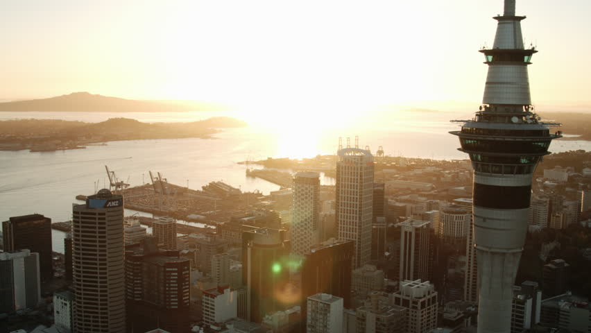 Sunrise drone shot of Sky Tower with Auckland in background.