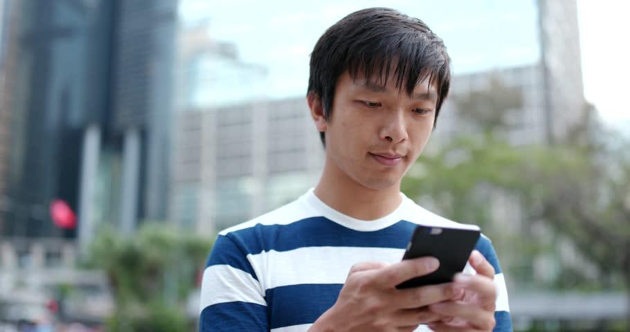 Asian man sending sms on cellphone #1009635008