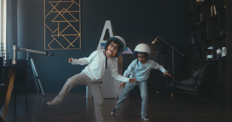 Cute little dreamer siblings boy and girl wearing space helmets pretending to be astronauts on Moon, getting out cardboard space rocket at home. 4K UHD 60 FPS SLOW MO | Shutterstock HD Video #1009647728