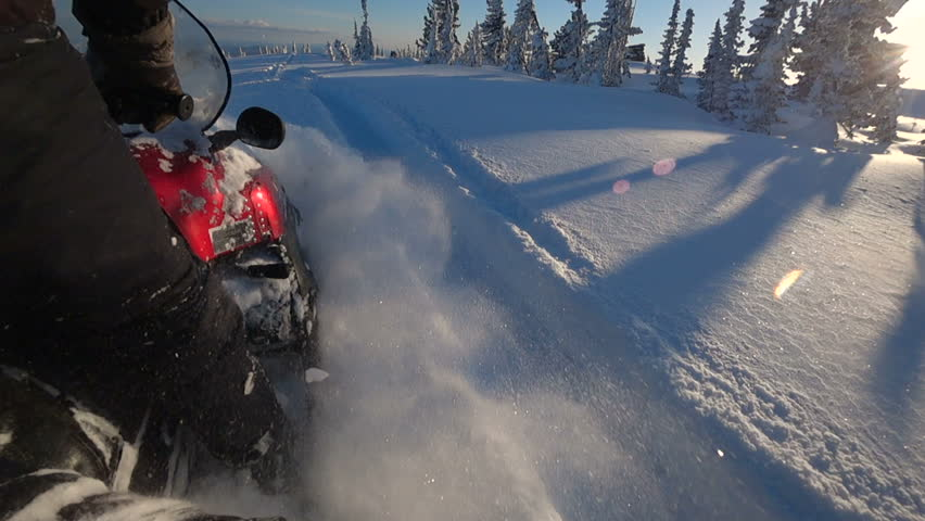 SLOW MOTION, CLOSE UP: Snowmobile takes off and sprays snow into the camera. Sled riding race in back country. Snowmobile tracks spinning, kicking up fresh snow and spraying snowflakes. Snowmobiling