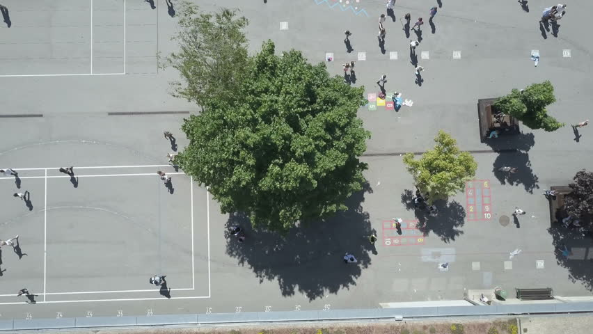 Kids playing in school playground during lunch break, Aerial Overhead Shot