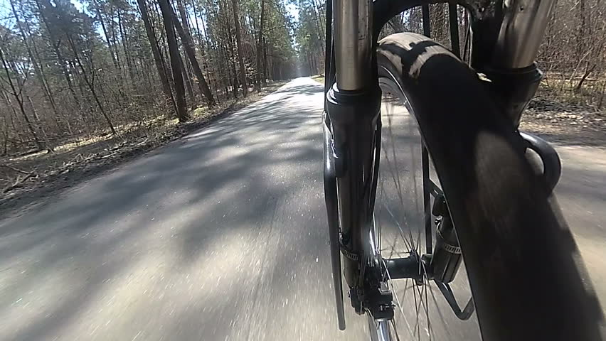 Wheel of  bicycle  with tyre goes on asphalt  road. Spring slow motion  #1009674920