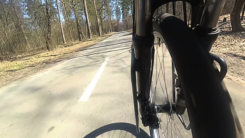 Wheel of  bicycle  with tyre goes on asphalt  road. Spring slow motion  #1009674923