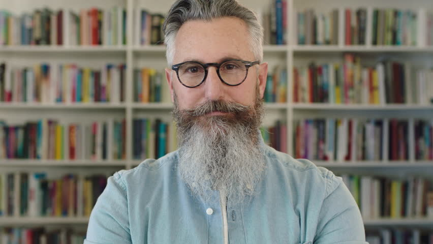 Portrait of mature caucasian professor with beard smiling happy at camera in library bookshelf background wearing glasses real people series   Shutterstock HD Video #1009697153