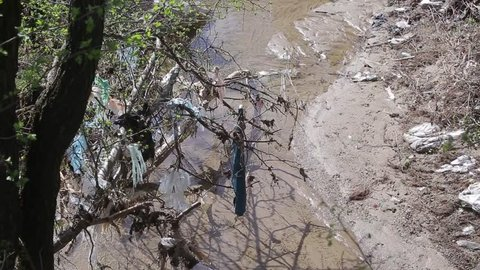 Heavy polluted water stream with domestic garbage