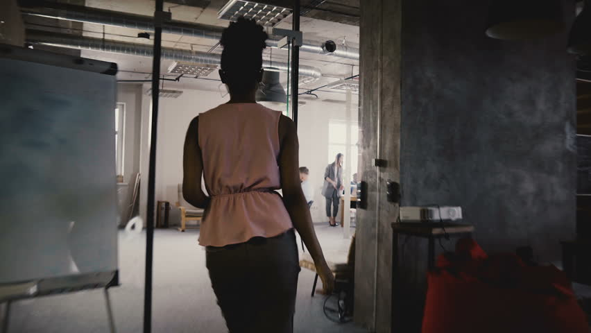 Camera follows happy black female leader enter office, talk to colleagues. Multiethnic colleagues in modern coworking 4K | Shutterstock HD Video #1009702583