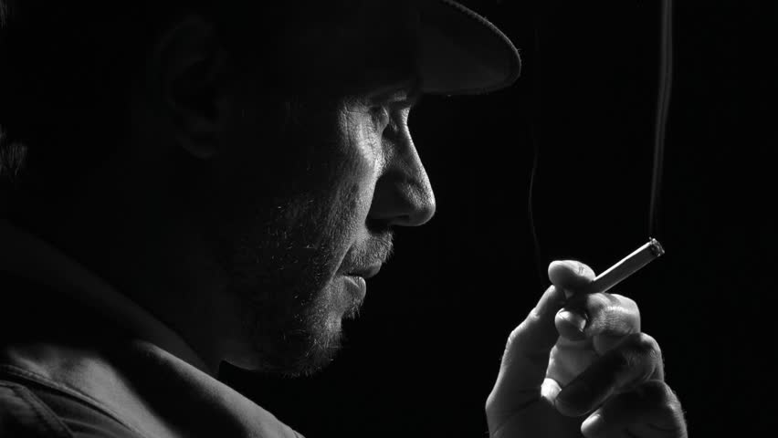 Confident noir detective smoking a cigarette, he turns and looks at the camera
