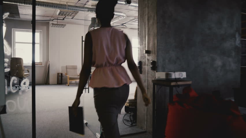 Camera follows African American female business coach enter office, motivate and inspire multiethnic workers team 4K.   Shutterstock HD Video #1009712111