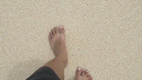 leg of a man walking on beach sand during vacation