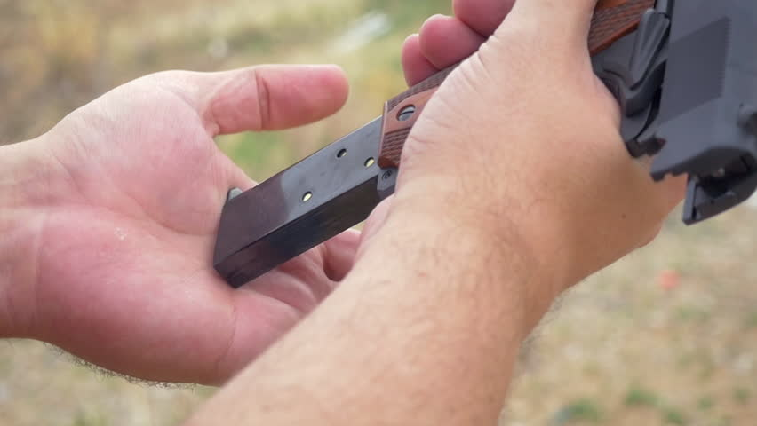 Man loading a handgun in slow motion. Closeup of a male inserting a magazine into a 9mm pistol and pulling the slide releasing a bullet into the chamber representing concealed carry and gun control.
