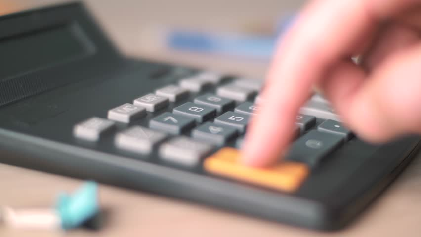 Hand calculating on a calculator | Shutterstock HD Video #1009717295