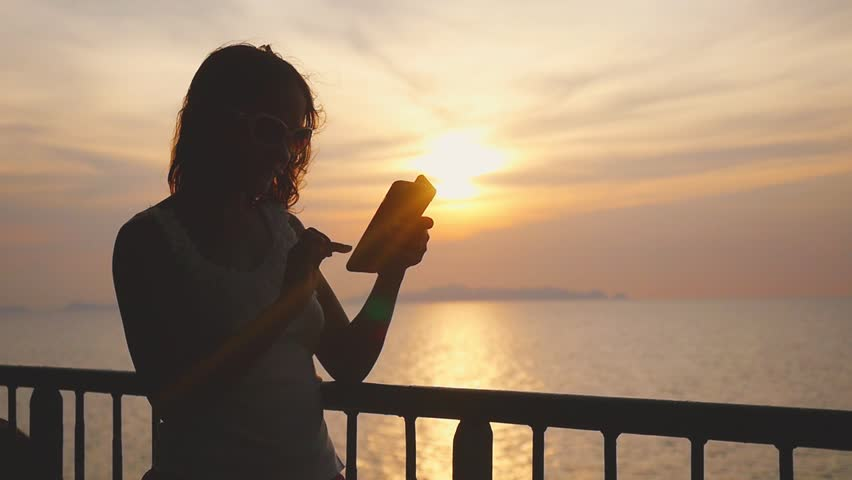 Young beautiful woman in sunglasses standing on deck of cruise ship and using her smart phone. Wind waving her hair. slow motion. 1920x1080