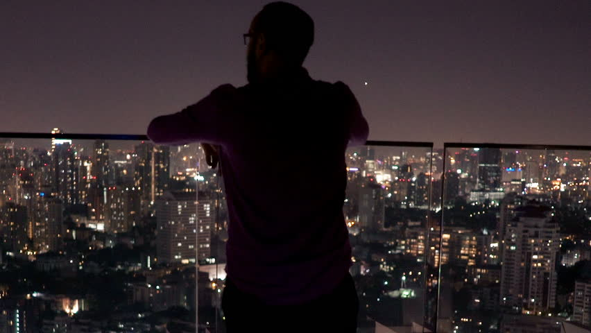 Young man admiring view from terrace during night