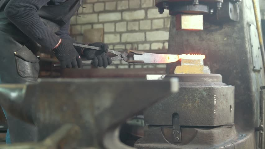 Man blacksmith forges the metal at the mechanical hammer   Shutterstock HD Video #1009725827